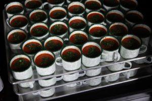Cold gazpacho ready to serve in spatterware enamel cups