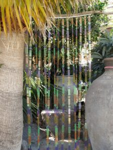 An outdoor shower gets a colorful beaded curtain.