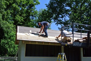 John and Oscar nail the cedar shingles to the roof. The black layer is roof felt. It is designed to temporarily waterproof the roof surface and is an essential element of roof installation.