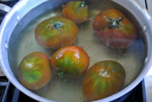 """Working in batches, Sanu and Laura scored an """"x"""" on each tomato and placed them in pots of boiling water - just long enough for the skins to start splitting."""