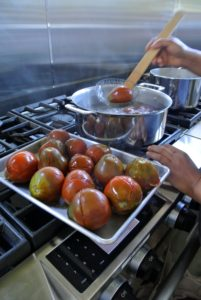 Once they are soft, and the skins start to separate, using a slotted spoon, or spoon colander, Sanu removed the tomatoes from the boiling water.