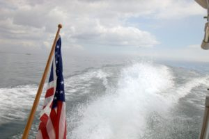 The flag signifies this is an American vessel. My Hinckley picnic boat creates a wake at 20-knots.