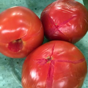 To remove tomato skins, first fill a bowl with ice and water and set it next to the stove. Drop tomatoes into the boiling water, and watch for their skins to wrinkle and split, then transfer to the ice water bath.