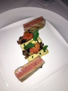 """The CAILLE is roasted quail breast, stewed peppers """"Basquaise"""", Ibérico ham, yukon gold potato, and braising greens."""