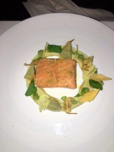 "This is the SAUMON, baked Alaskan king salmon ""in clay"", eucalyptus, artichokes, crispy socca, with a lemon balm emulsion."