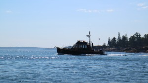 Here is a stealth black boat moving briskly through the water.