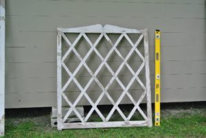 The smallest trellis would be hung in the center, and then two taller trellises would be positioned on each side.