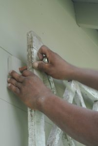 Using a ratchet, Pete tightens each bolt into the wall.