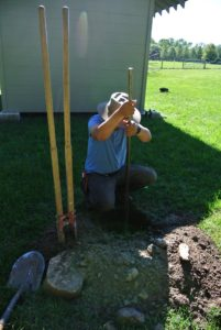 Using a tamping bar, Chhiring compacts the soil in the hole, so it is level.