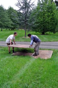 Pete and Jonah put plywood boards down to help make it easier for the truck to pass over the ditch on the side of the carriage road.