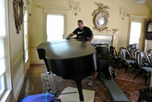 Once the piano lid is lowered and locked, Brian holds the piano while Sean removes the left front leg.