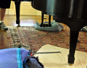 They then placed a moving blanket under the pedals to cushion it and to help balance the piano.