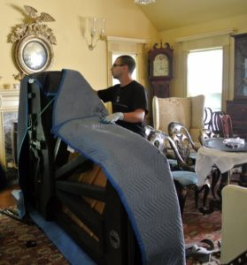 Several moving blankets are placed over and around the piano to give it as much cushioning as possible.