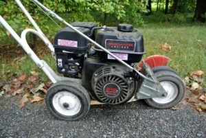 Power edgers are easy to use - just line up the edger blade on the turf side of the road, and turn it on. On this gas powered machine, one has to pull a cord to start the motor.