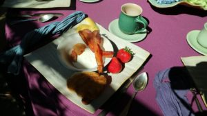 A colorful and delicious affair with croissants, bacon, strawberries, yogurt, and cappuccino.