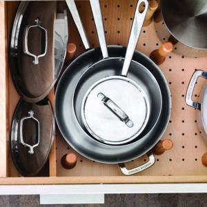 Keep pots and pans organized in pull out drawers fitted with pegs.