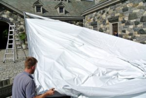 Once the end unit is secured, Zachary begins to attach the fabric - it's a very durable vinyl.