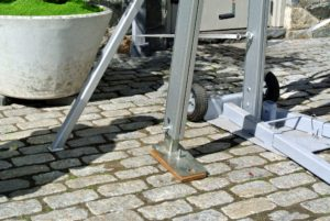 Base plates are at the foot of every upright support. Because the courtyard is cobblestone, stakes were not an option. These bases are very strong. Wooden shims protect the stone and also help to balance the bases.