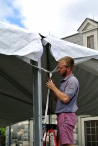 Zachary attaches the corners of each fabric section to the upright supports.