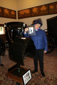 Here, Mary is holding a photo of a mechanical horse, and standing in front of an actual mechanical horse.