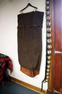 This is a special lap robe used while riding in a sleigh - and look, it has its original sleigh bells.