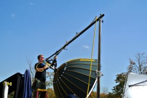 The crew sets up this giant parabolic umbrella, which helps to diffuse the bright light.