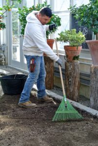 Wilmer uses a lawn rake to tidy up the top layer of soil and to give it a finished look.