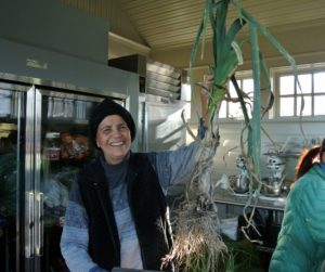 Laura holds one of the large leeks, ready to be washed. Thorough washing is very important for leeks, as soil is often trapped between the many layers of leaves.