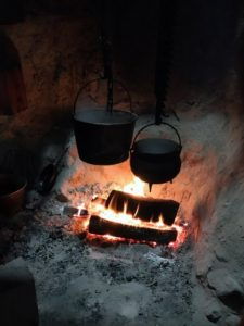 Cast iron pots are used to cook directly over the hearth.