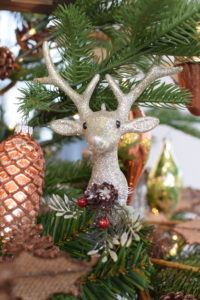 We call this our Glittered Deer ornament - a colorful embellishment featuring a deer with faux berries and a pinecone on a leafy branch.