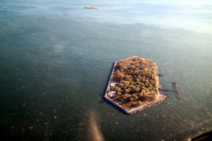 This hexagon-shaped island is Hoffman Island - one of two small artificial islands off Staten Island, New York. The other, smaller island, is called Swinburne Island, and can be seen in the distance. In the early 1900s, the islands were used as a quarantine station, housing sick immigrants, with contagious diseases, when they landed at Ellis Island.