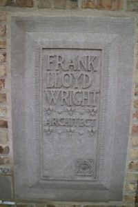 "Adjacent to the studio entrance, a stone plaque announces ""Frank Lloyd Wright, Architect."" The plaque features Wright's first logo, with a cross and circle within a square - pure geometric forms found throughout Wright's architecture, and repeated in elements such as the four urns atop the wall in front of the Studio."
