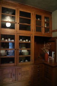 Located between the original kitchen and dining room, the pantry is a functional space filled from floor to ceiling with built-in cabinets and shelves.