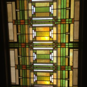 The entrance hall to the studio presented a notable first impression of the building to arriving clients. The skylight, added in 1905, features a complex geometric design in a palette of gold and green iridescent glass. The design is exemplary of Wright's ability to render the natural world abstractly.