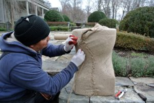 Wilmer sews from the base to the top, making sure the burlap fits snug around the container as he goes.