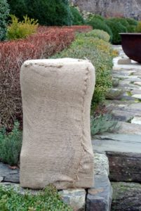 The burlap nearly conforms to the shape of the urn.