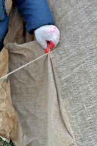 Chhiring sews one side together, making small knots first, so the fabric is secure as he sews.