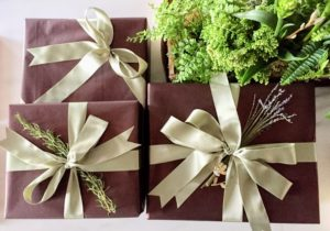 I love this deep chocolate brown paper with the shiny satin ribbon embellished with sprigs of herbs. Keep your tissue paper, twine, and wrapping paper organized and accessible in bins so it's easy to find year after year.