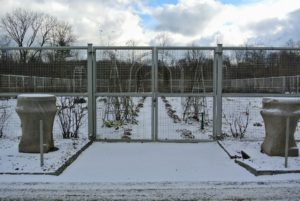 And here's my flower cutting garden under a coating of white. This is the fence surrounding the cutting garden, located behind the greenhouse. A pair of stately Kenneth Lynch garden urns at this entrance are covered in burlap for the winter.