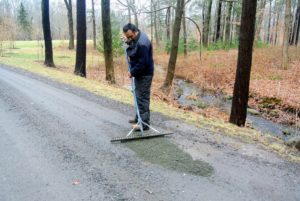 Pete follows with a rake to spread and blend the gravel into the surrounding areas of the carriage road.