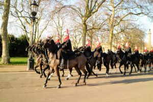 These are the Blues and Royals, or Royal Horse Guards and 1st Dragoons, part of the Household Cavalry. During poor weather, they wear long blue cloaks with red collars. Except for the Trumpeters who ride greys, the Blues and Royals ride black horses.
