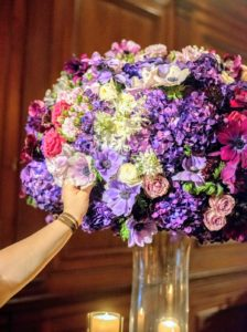 Rising from the center of the table is a vivid floral arrangement.  (Photo by Chudleigh Weddings)