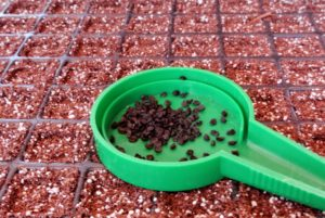 Using a hand seed sower, such as this one from Johnny's Selected Seeds, pour a generous amount of seeds into the center dish.