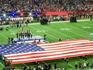 Then, the American Flag was displayed on the field as country music singer and songwriter, Luke Bryan, sang the national anthem.