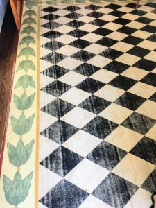 The rectangular entrance hall has a black and white diamond patterned floorcloth edged with a leaf motif.