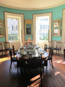 Off the central stair hall is the oval dining room, with turquoise walls that look painted, but are actually small squares of unpatterned wallpaper.