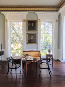 The large rectangular withdrawing room found at the front of the house has soft gray walls, white wainscoting and multilayered gilded cornice molding.