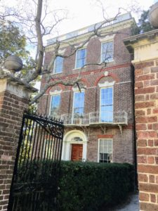 The house and grounds are separated from the street by a brick and wrought iron fence and entrance gate.