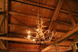 The ceilings are vaulted and adorned with antler chandeliers. There is also  a warm stone hearth for guests to enjoy.