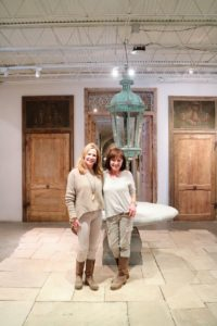 Here is Ruth with Shawnna Fatjo, team member of Domingue Architectural Finishes. They're standing on reclaimed Italian cathedral stone, and in front of a bespoke, newly-quarried Belgian blue stone table. Behind them is a giant 19th century copper lantern from Macon, France and a pair of 18th century doors.